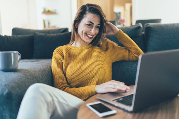 Relax at home Beautiful young woman relaxing at home drinking coffee and surfing the net only young women stock pictures, royalty-free photos & images