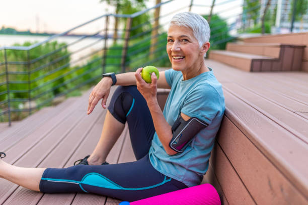 Relax concept Sporty woman eating apple. Beautiful woman with gray hair in the early sixties relaxing after sport training. Healthy Age. Mature athletic woman eating an apple after sports training active seniors stock pictures, royalty-free photos & images