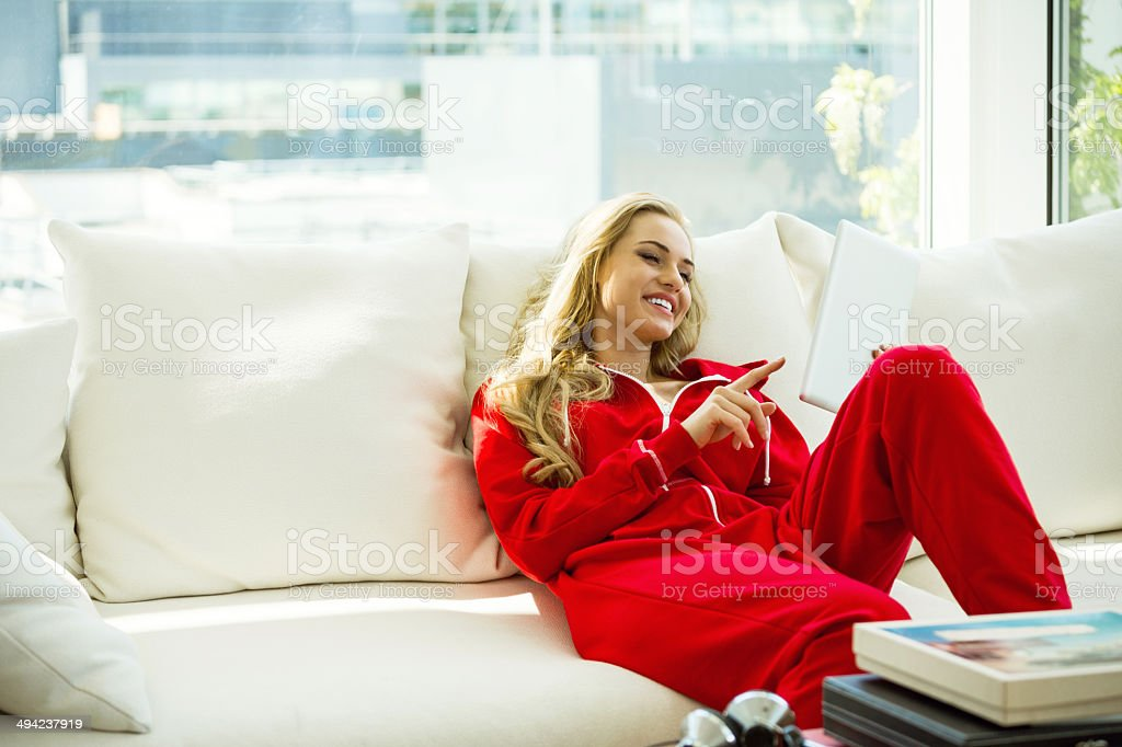 Relax in the morning Young woman relaxing on sofa at home and using a digital tablet in the morning. 20-24 Years Stock Photo