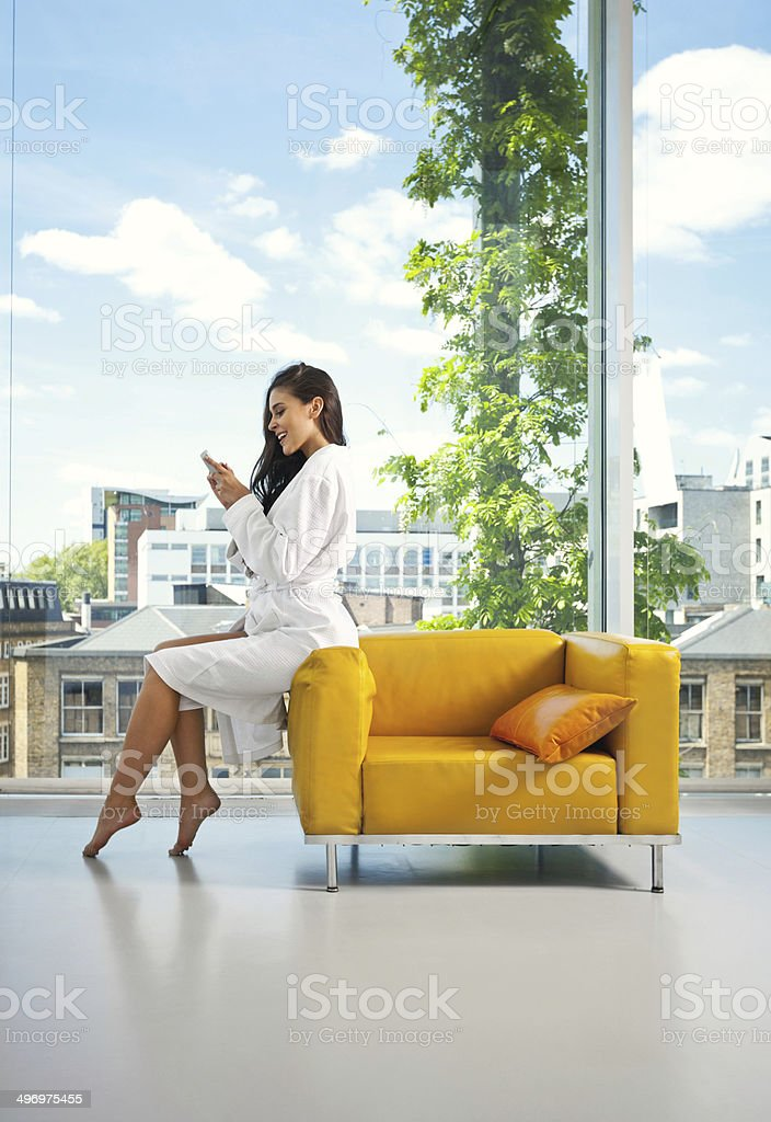 Relax in the morning Beautiful young woman wearing white bathrobe relaxing on armchair in her apartment in the morning, using a smart phone. 20-24 Years Stock Photo