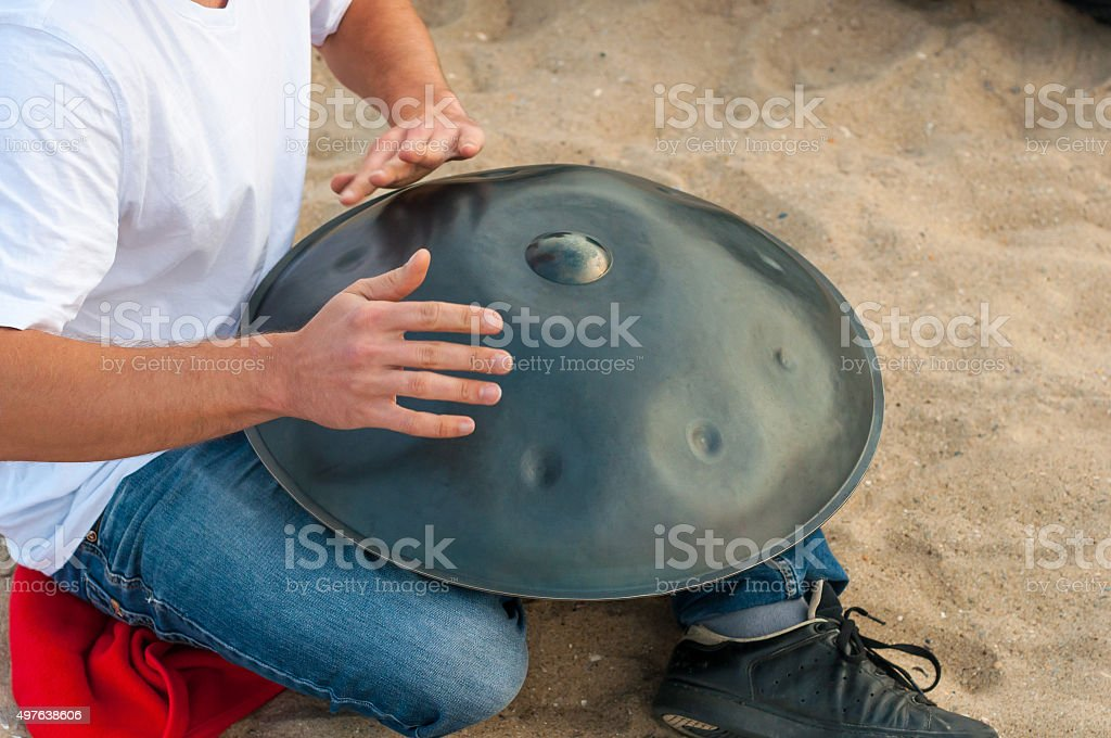 Relax music background. Hands percussion. Musician sit on sand and stock photo
