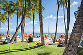 Waikiki, Oahu - August 10th 201 7, People lying on the beach sunbathing under parasol and palm trees at Waikiki shore.