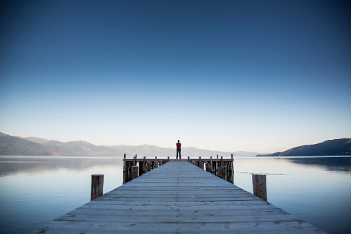 Man has relaxing in beautiful landscape on pier at sunset in lake Ohrid,Macedonia.