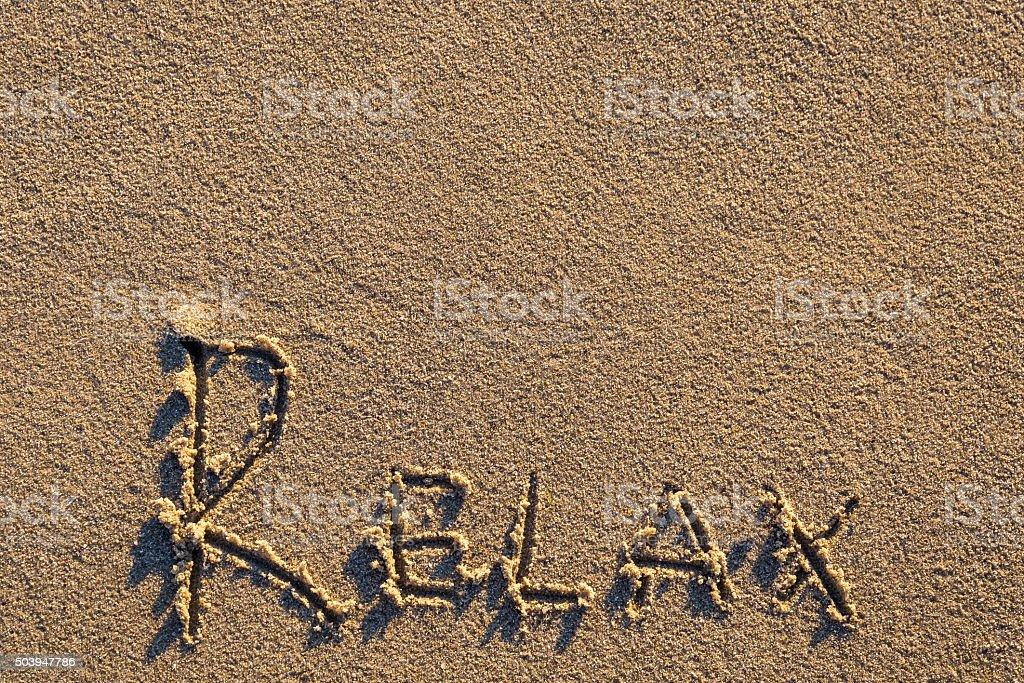 'Relax' written on the beach stock photo