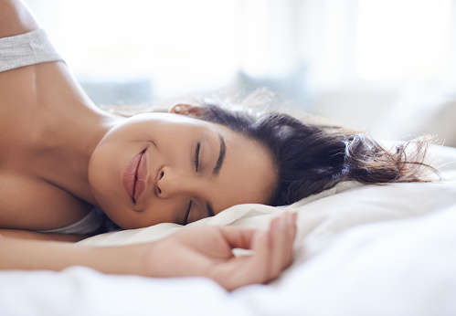 Shot of an attractive young woman relaxing on her bed in the morning at home