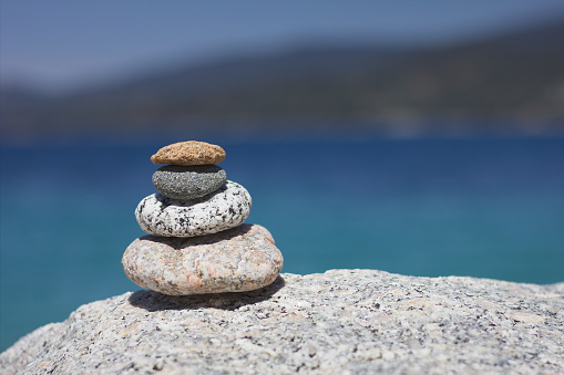 Relax Zen stones. Background sea for the perfect meditation. Stones pyramid in the sun