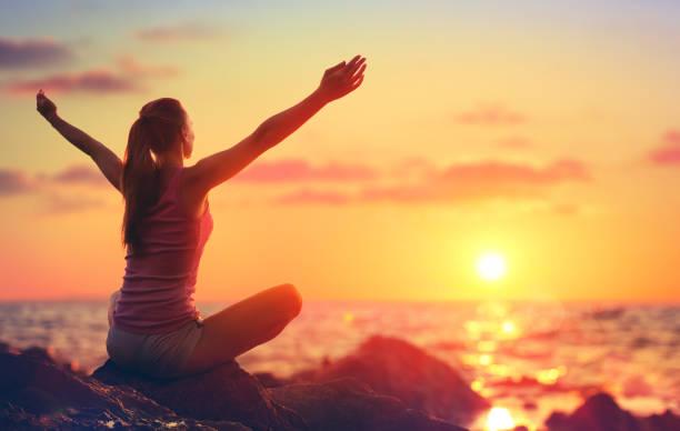 Entspannung und Yoga bei Sonnenuntergang - Mädchen mit offenen Armen Ozean suchen – Foto