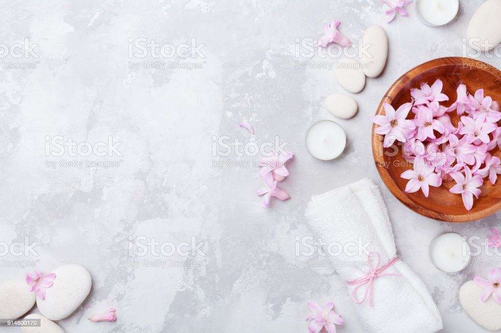 Relaxation and zen like concept. Aromatherapy, beauty and spa background with massage pebble, perfumed flowers water and candles. stock photo