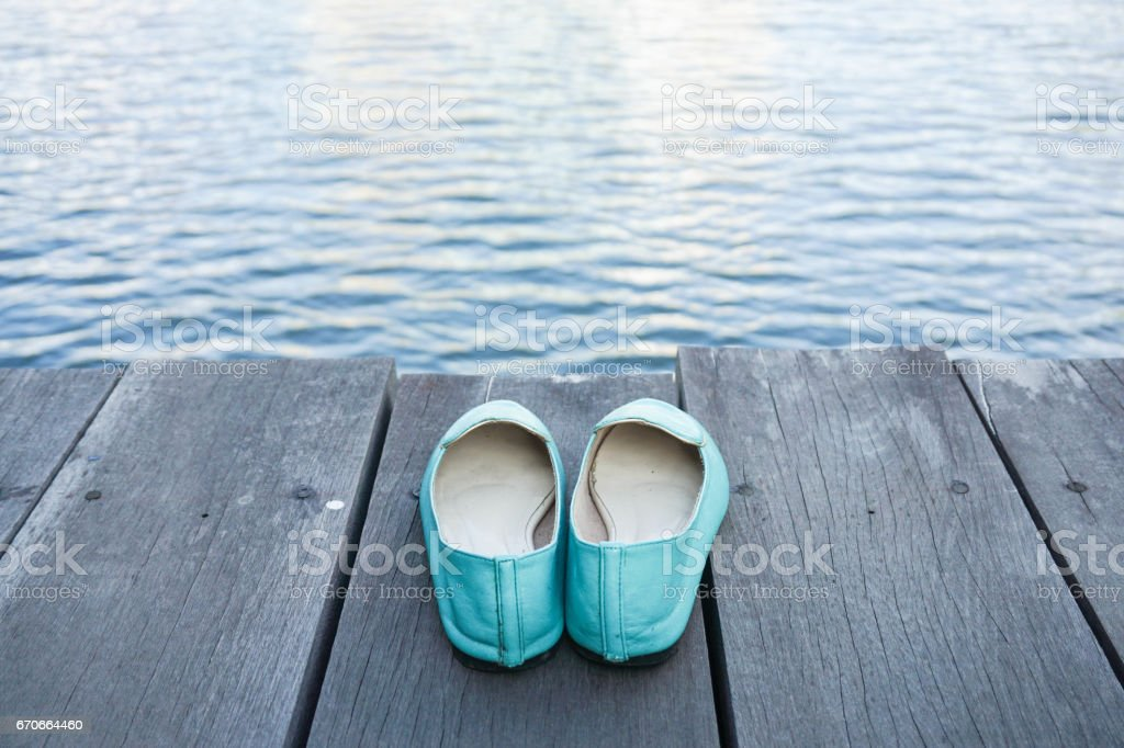 relaxation concept of green shoes on the wooden walkway with water in front stock photo