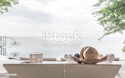 Relaxation holiday vacation of businessman take it easy happily resting on beach chair at swimming pool poolside beachfront resort hotel with sea or ocean view and summer sunny sky outdoor
