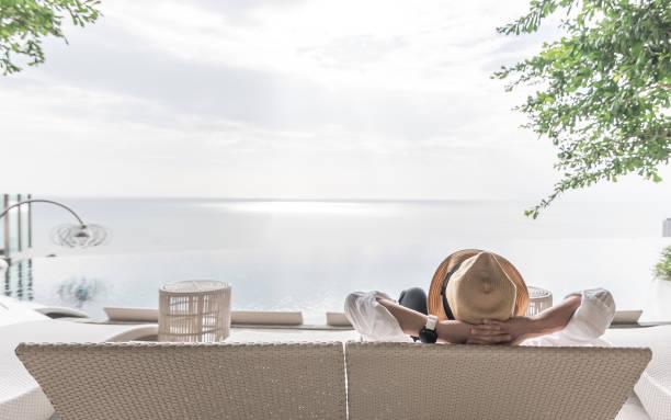 wakacje relaksacyjne biznesmen wziąć to łatwe szczęśliwie odpoczynku na leżaku w basenie przy basenie nadmorski hotel resort z widokiem na morze lub ocean i letnie słoneczne niebo na zewnątrz - kurort turystyczny zdjęcia i obrazy z banku zdjęć