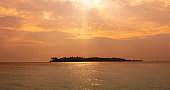 Sun rays in sunset sky on tropical island. Relaxing vacation at the Maldives.