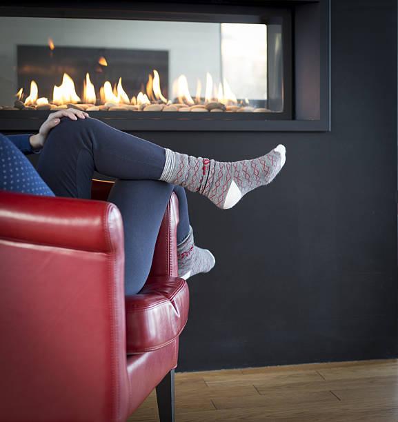 relaxation near fireplace - gaskamin stock-fotos und bilder