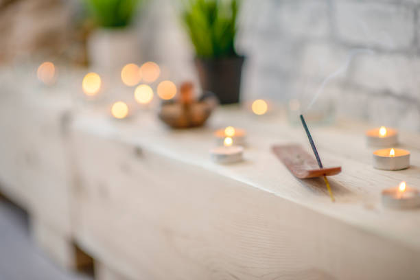 Relaxation Several tea light candles and an incense stick are lit and spread out along a wooden beam. incense stock pictures, royalty-free photos & images