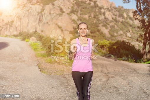 Horizontal color image of beautiful woman running in scenics rocky mountains and listening music. Vital young woman wearing pink tank top, arm band and wristwatch. Sportswoman enjoying beautiful sunset.
