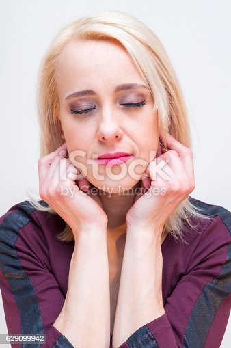 Relaxation techniques. Young blonde woman holding earlobes with eyes closed.