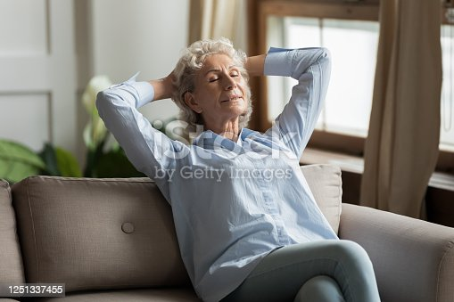 973962328 istock photo Relaxed 55s woman leaned on couch daydreaming in living room 1251337455