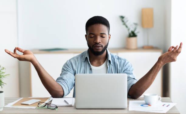 homem de negócios relaxed do americano africano que meditando no escritório - consciencia negra - fotografias e filmes do acervo
