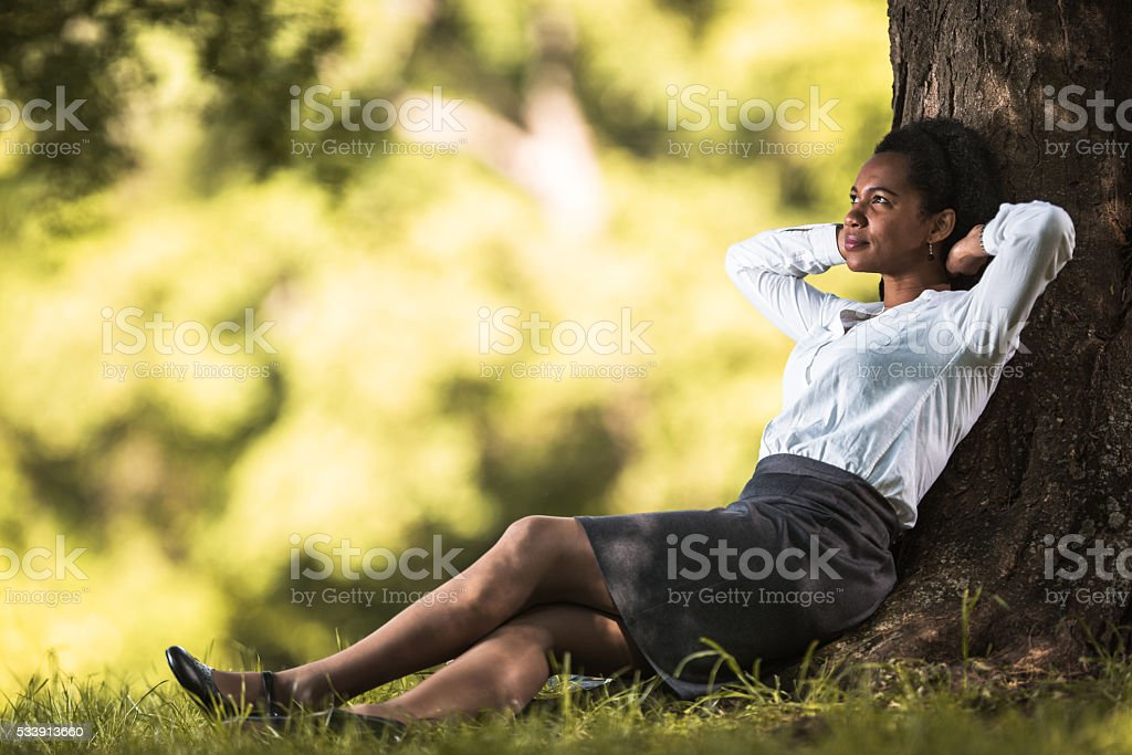 Mid adult African American businesswoman sitting in nature with hands...