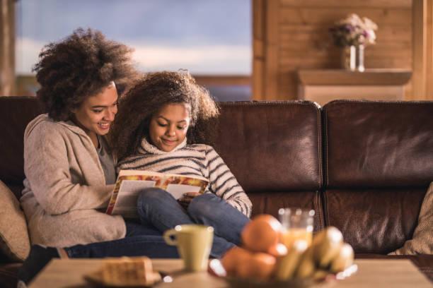 entspannte afroamerikanische mutter und tochter ein buch auf dem sofa. - behaglich stock-fotos und bilder