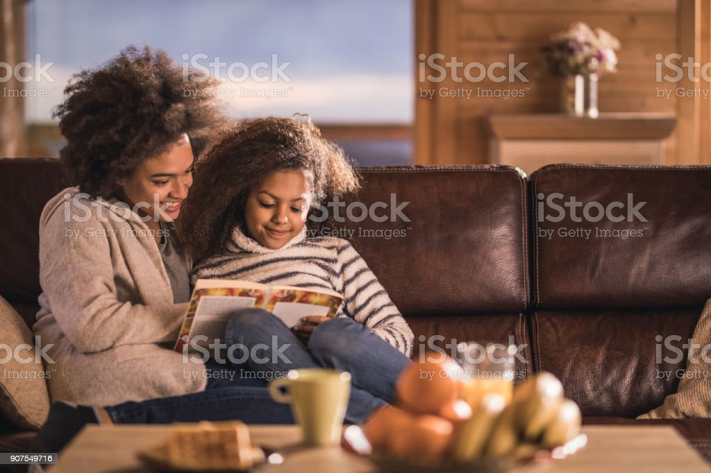 Relaxed African American mother and daughter reading a book on sofa. stock photo