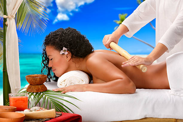 Relaxed African American woman getting bamboo massage therapy beach Spa stock photo