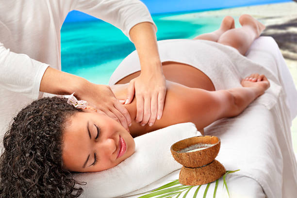 Relaxed African American woman getting massage therapy beach Spa stock photo