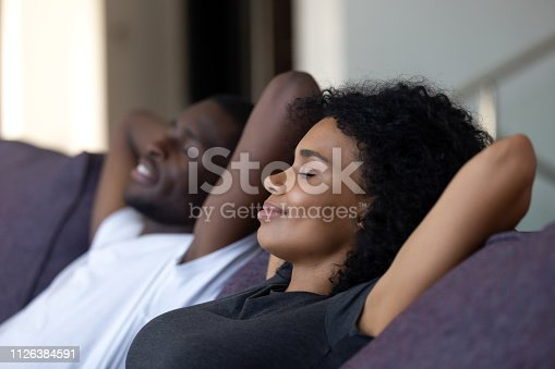 istock Relaxed african couple enjoying breathing fresh air on comfortable couch 1126384591