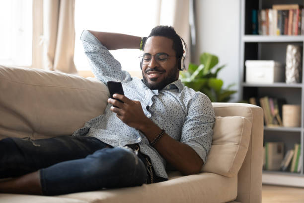 Relaxed african man wear headphones chill on sofa listening audiobook Relaxed millennial african man wear wireless headphones chill lying on sofa listening audiobook on smartphone, smiling young adult afro american guy rest on couch enjoying mobile music in app at home wireless headphones stock pictures, royalty-free photos & images