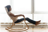 Near panoramic window african woman resting on comfortable position and angle wooden rocking chair enjoy free time lazy weekend in living room at home side profile full length view, no stress concept