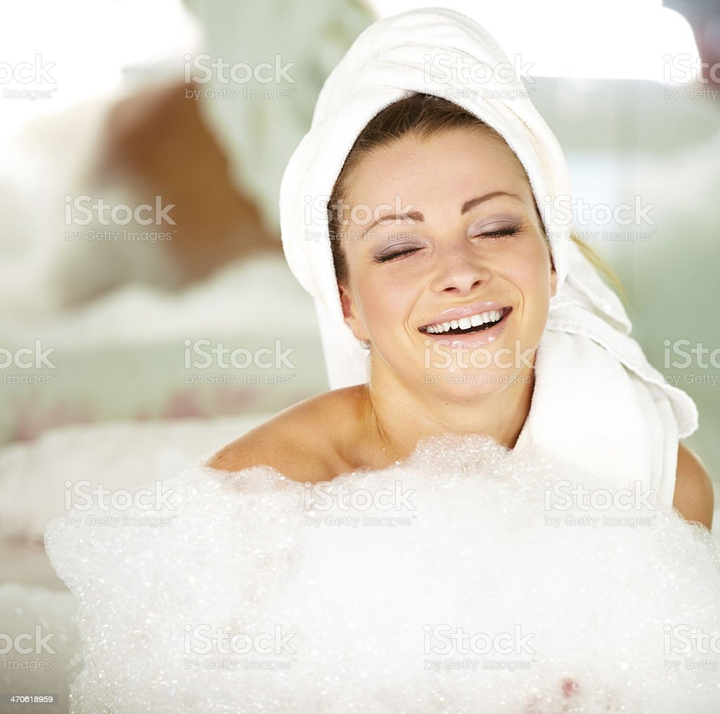 Relaxed and smiling young woman lying in a bath royalty-free stock photo