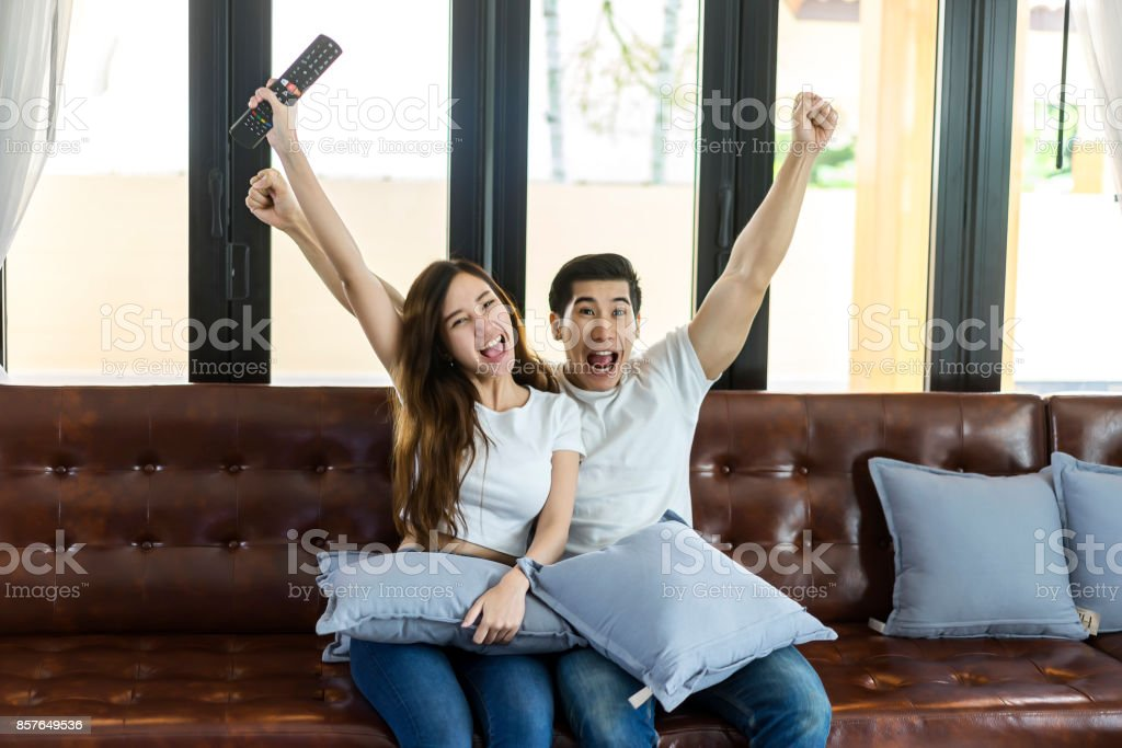 Relaxed asian young couple having fun watching at home in bright living roomWoman using  sc 1 st  iStock & Relaxed Asian Young Couple Having Fun Watching At Home In Bright ...