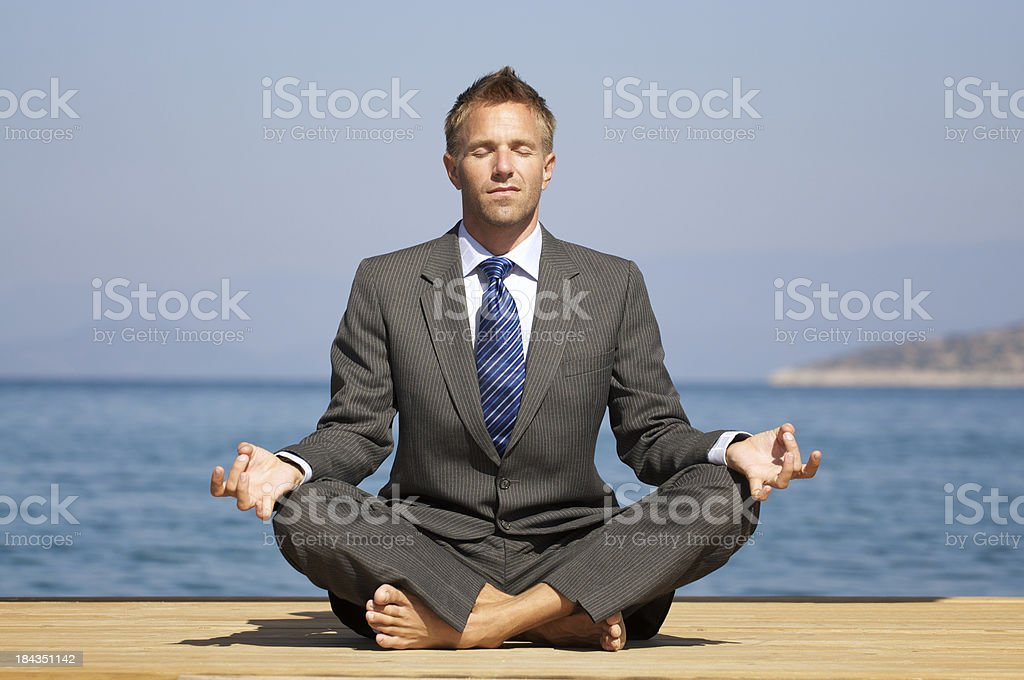 Relaxed Barefoot Businessman Doing Yoga on a Sunny Dock stock photo