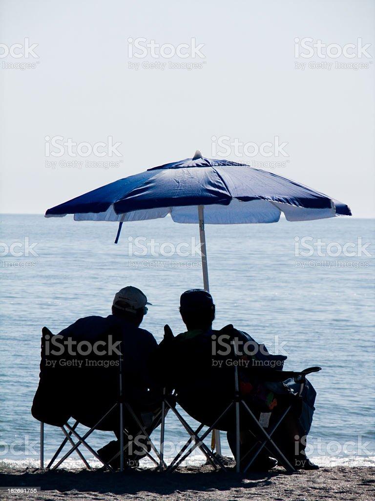 Relaxed Beach Conversation Under Blue Umbrella royalty-free stock photo