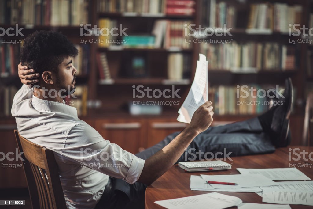 Relaxed black businessman reading business reports at his home office. stock photo