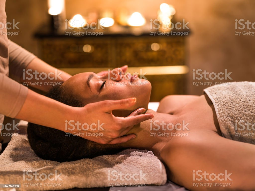 Relaxed black woman having facial massage at the spa. stock photo