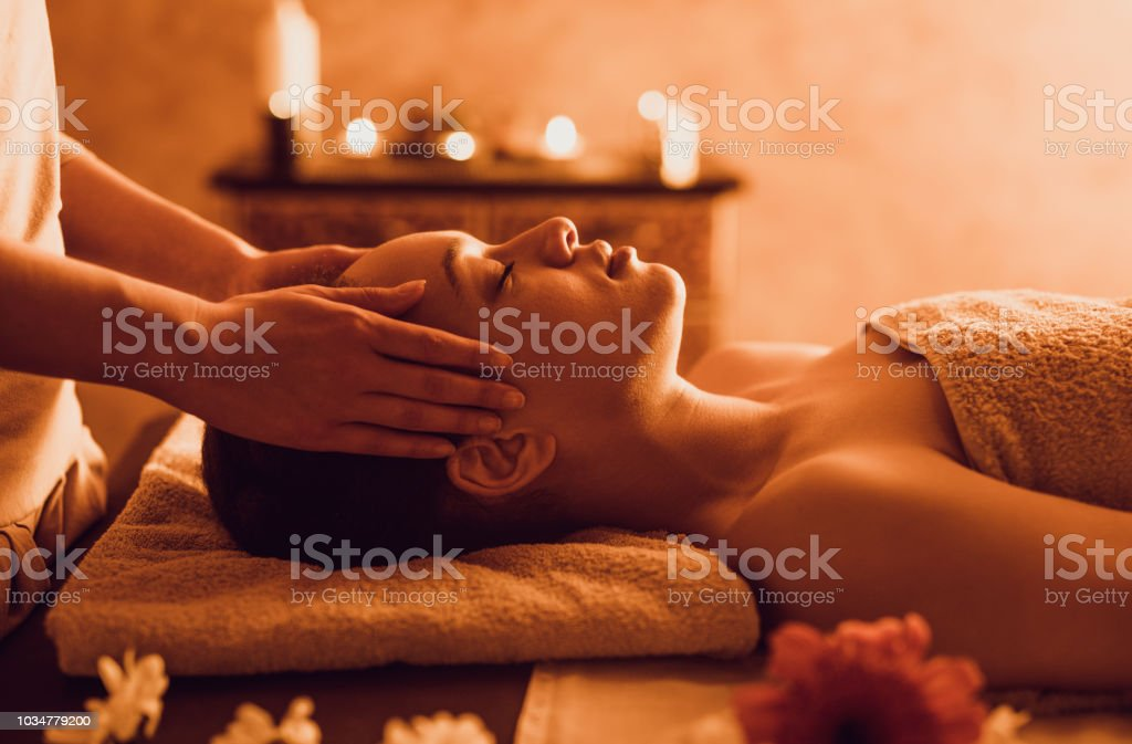 Relaxed black woman having head massage at the spa. stock photo