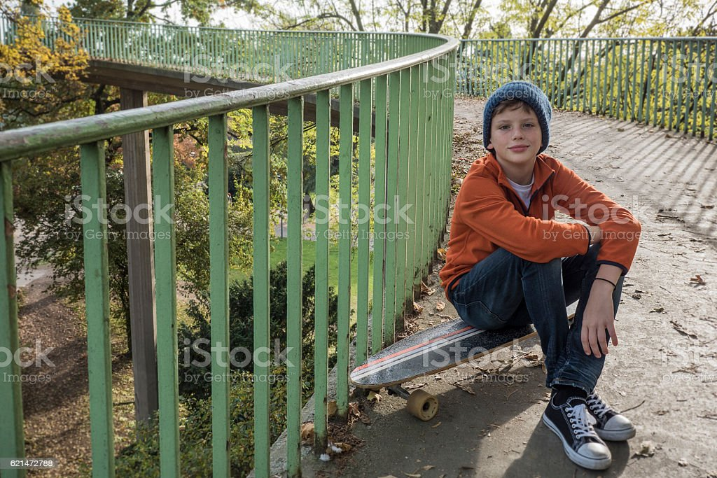 Relaxed boy with skateboard looking at camera stock photo