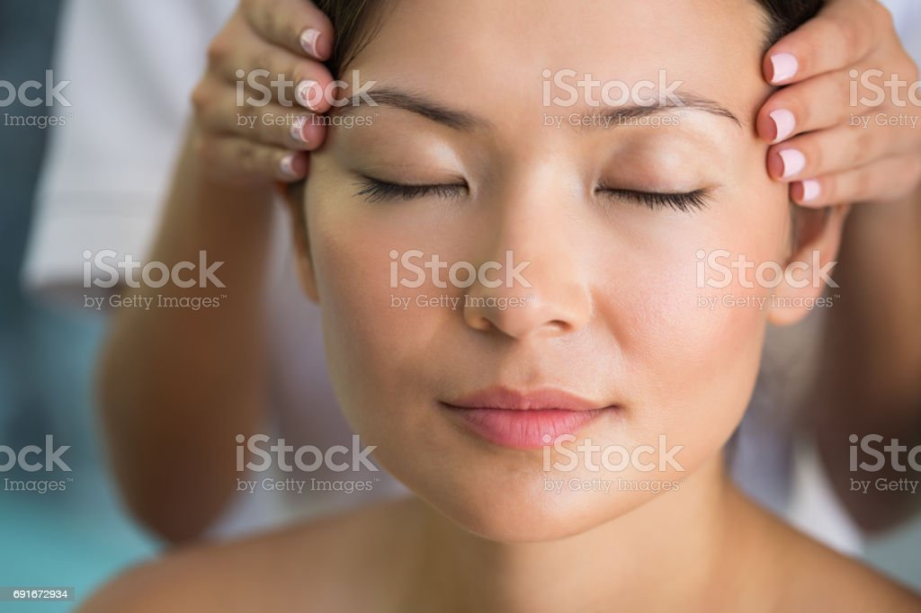 Relaxed brunette getting a head massage stock photo