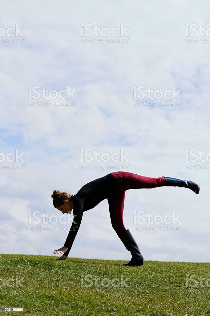 Russian outdoor girl in jacket trousers handstand stock photo