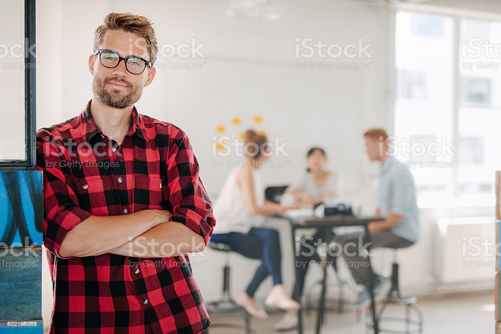 Relaxed business man in office with colleagues in background Portrait of relaxed young man standing in office with colleagues meeting in background. Adult Stock Photo