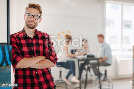 624700110istockphoto Relaxed business man in office with colleagues in background 622196388