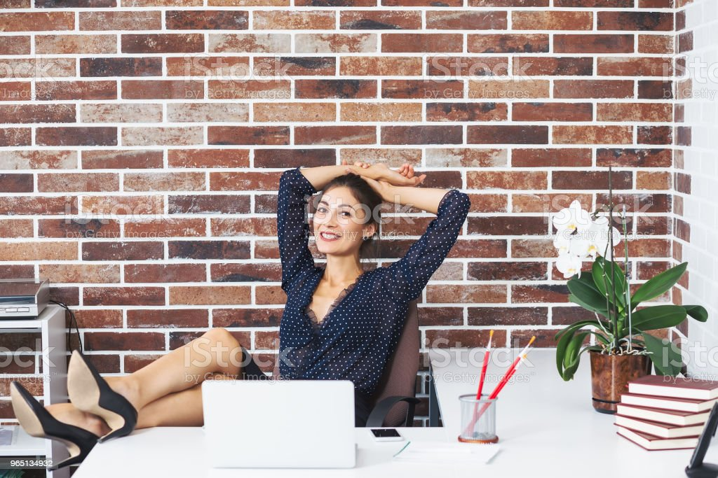 Relaxed business woman with legs on the desk in office smiling zbiór zdjęć royalty-free