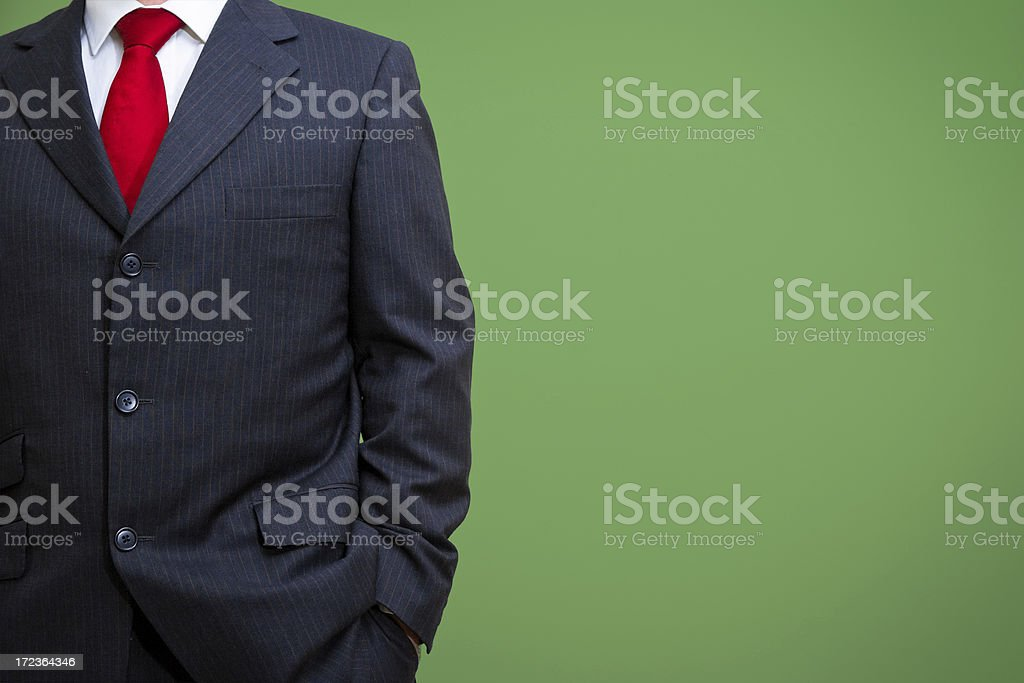 """Relaxed businessman in suit """"Relexed businessman with hand in pocket, dressed in smart suit against a green wall."""" 20-29 Years Stock Photo"""
