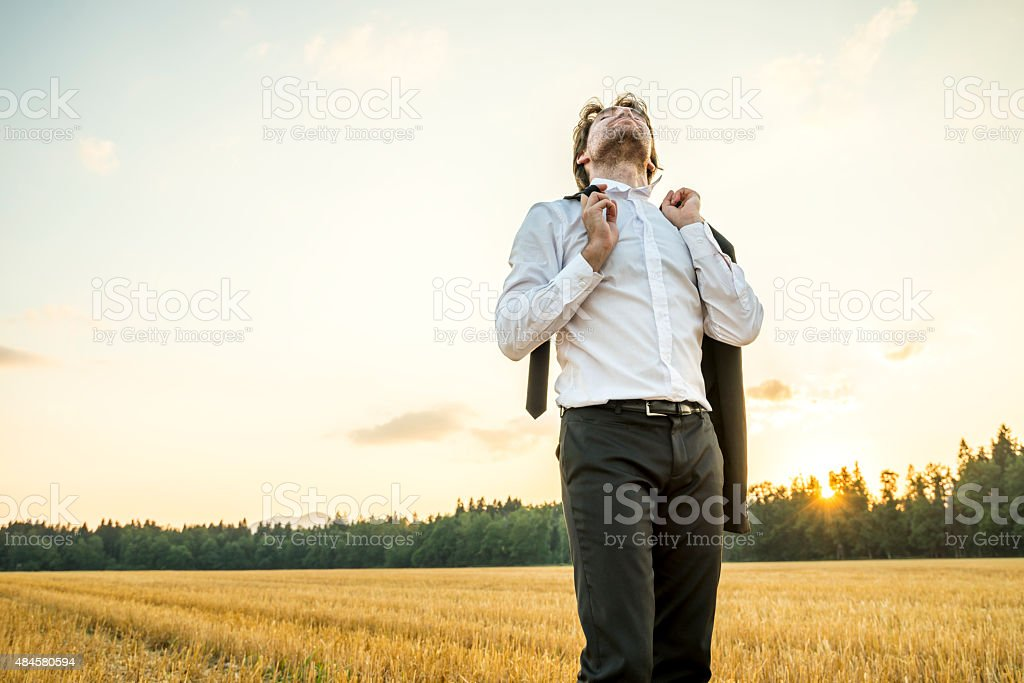 Relaxed businessman in white shirt standing in  wheat field stock photo