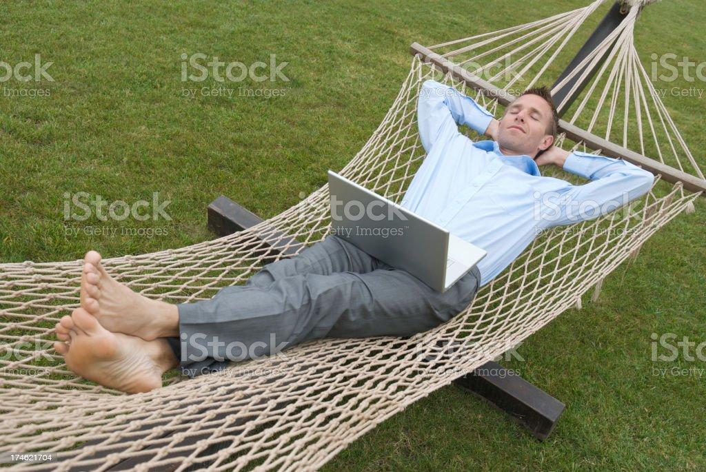 Relaxed Businessman Lying Back for Siesta in Hammock stock photo