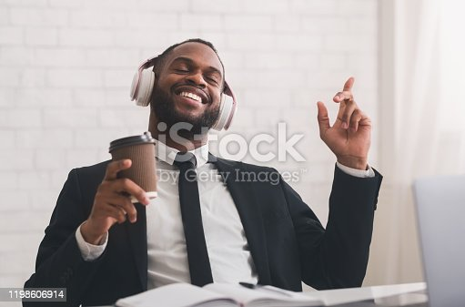 1003539592 istock photo Relaxed businessman singing, listening to music and drinking coffee 1198606914