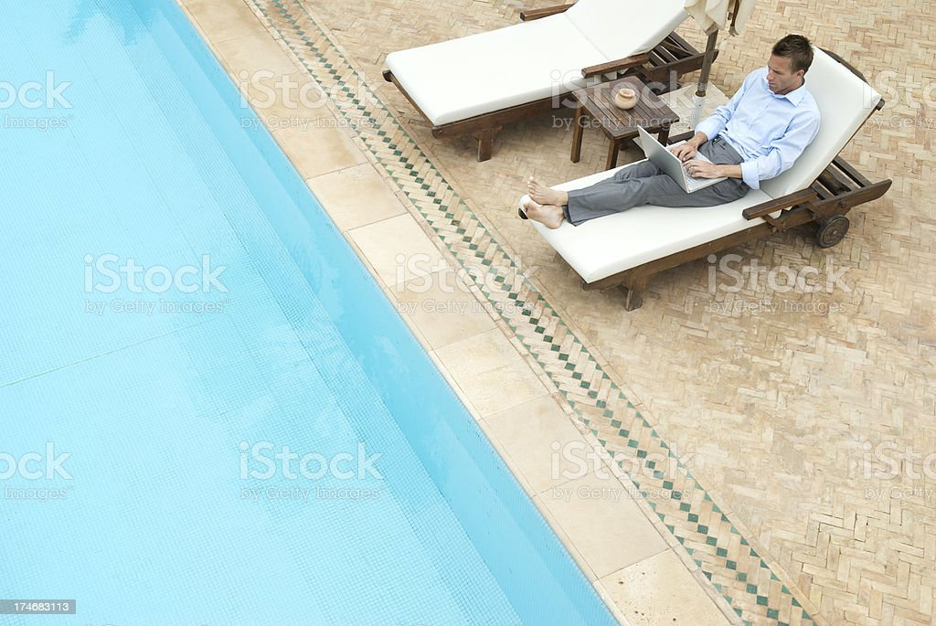Relaxed Businessman Sitting Poolside Working on Laptop royalty-free stock photo