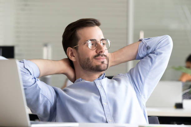 Relaxed businessman taking break holding hands behind head enjoying rest Relaxed confident business man taking break from work on laptop for mind relief holding hands behind head thinking of success enjoying rest, good result of job done in office, no stress free concept relief emotion stock pictures, royalty-free photos & images
