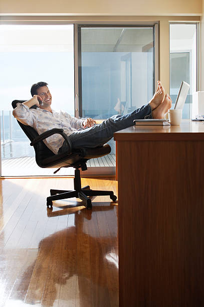 Relaxed Businessman Using Cellphone In Home Office stock photo